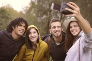 happy diverse friends taking selfie in park